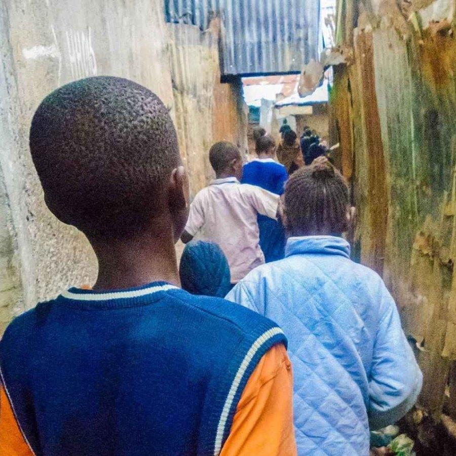 Kinder gehen einen engen Gang in den Kiberia-Slums entlang