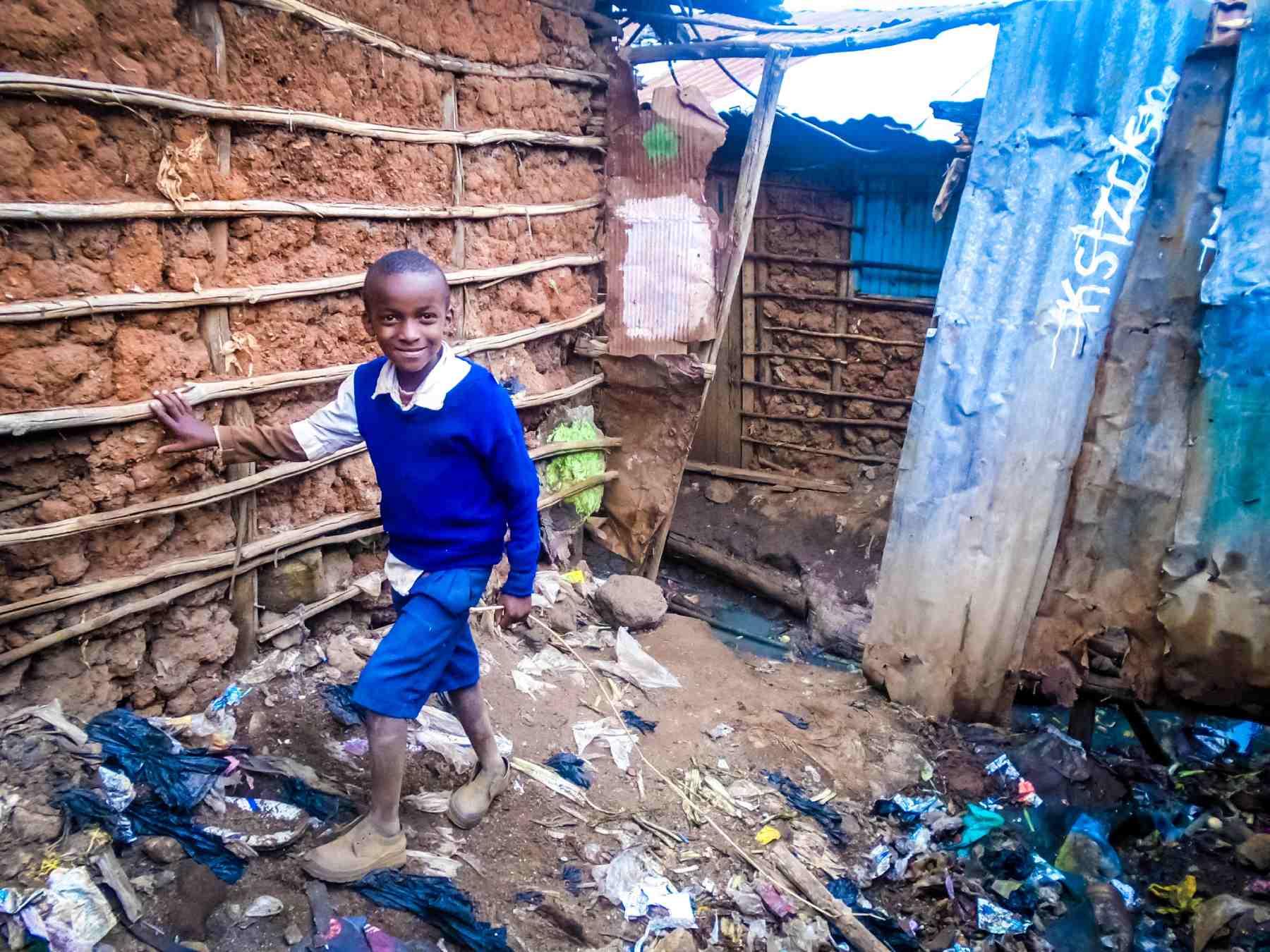 Ein junge in blauer Kleidung lehnt lächelnd an einer Wand aus Lehm, von Müll umgeben