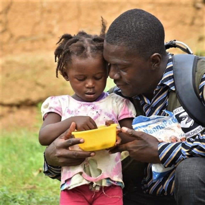 Mann hält lächelnd ein kleines Mädchen mit Essen
