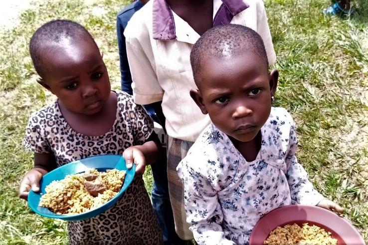 Zwei Kinder halten Teller mit Essen